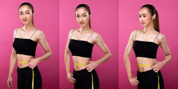 Asiatische schlanke fitnessfrau zeigt ihre kleine dünne taille mit maßband. mädchen kontrolliert fett und isst gesundes essen. studiobeleuchtung rosa hintergrund isoliert, konzept frau kann sportler sport gesund machen
