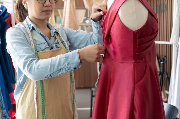 Asiatische schneiderin modedesignerin, die größe der schaufensterpuppe im ausstellungsraum misst.