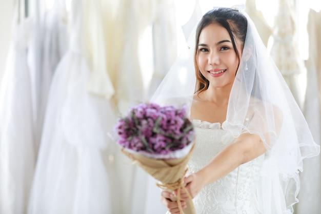 Asiatische schöne braut im weißen kleid mit durchsichtigem haarspitzenschleier, der lächelnd in die kamera schaut, die lila duftenden hochzeitsblumenstrauß in den händen in verschwommenem vordergrund in der umkleidekabine hält.