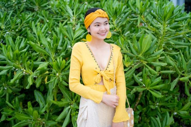 Asiatische schöne frau, die ein kleid am strand trägt.