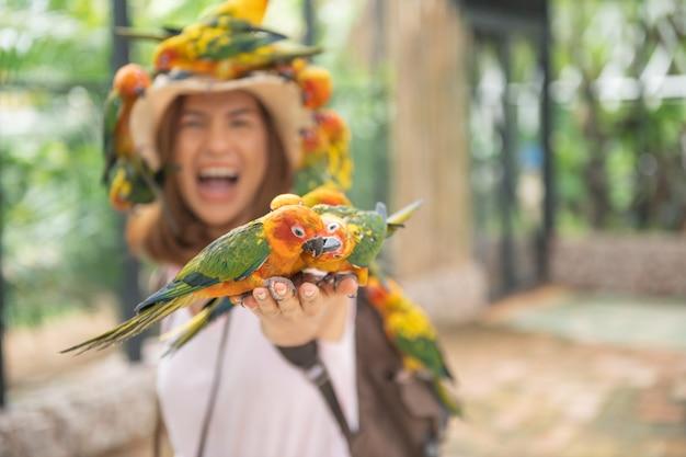 Asiatische schöne frau, die mit liebesvogel an hand genießt