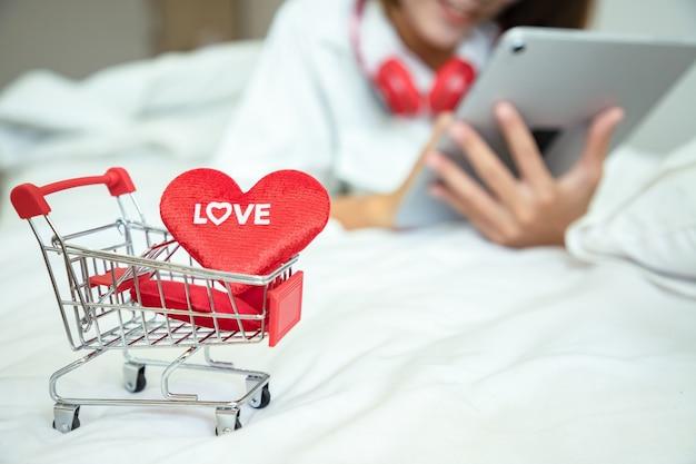 Asiatische schöne frau, die tablette verwendet, um geschenke am valentinstag und einkaufswagen mit herzliebetext zu kaufen