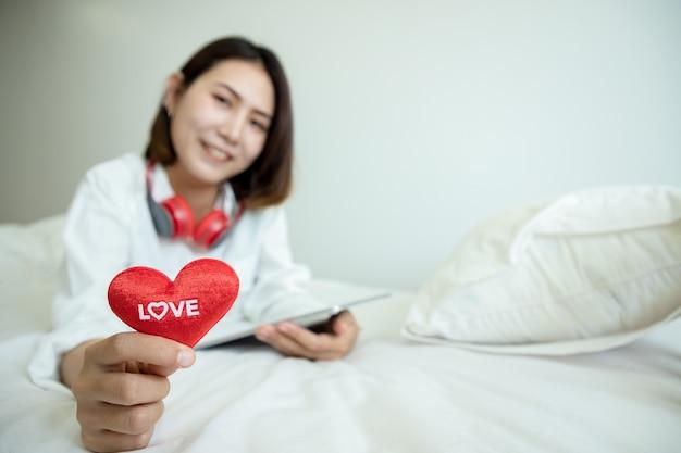 Asiatische schöne frau, die tablette verwendet, um geschenke am valentinstag zu kaufen und herzen lieben text auf schlafzimmer zu zeigen