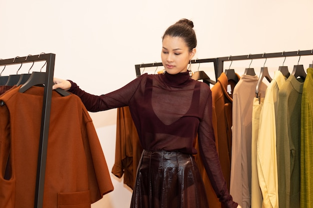 Asiatische schöne frau im kleid wählt neue kollektion auf orangegrünem erdton-kleiderständer im modegeschäft aus, das nur markennachrichten für den winterherbst als minimalen stil öffnet