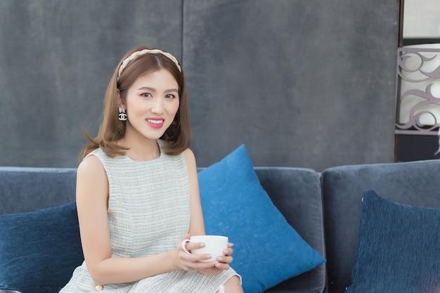 Asiatische schöne frau in einem kurzärmeligen kleid sitzt glücklich und trinkt heißen kaffee oder heißen tee auf einem dunkelblauen sofa in einem eleganten restaurant an einem schönen nachmittag.