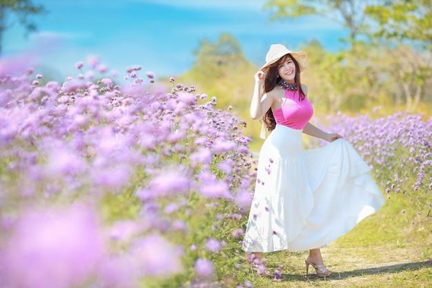 Asiatische schöne frau, langes haar im niedlichen kleid auf verbena im winter mit blauem himmel abgelegt.