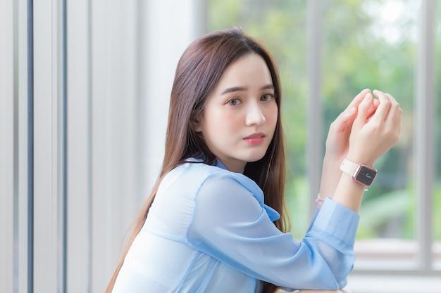 Asiatische schöne frau trägt blaues hemd und intelligente uhr und sitzt in der nähe des fensters als hintergrund.