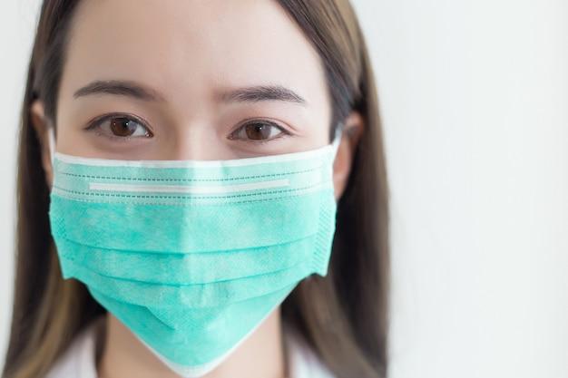 Asiatische schöne frau trägt eine chirurgische maske, um das coronavirus zu schützen