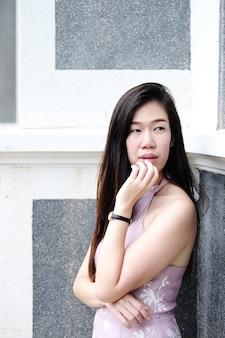 Asiatische schöne frau trägt kleid rosa und lächelt und postet für street fashion in der stadt