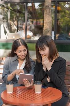 Asiatische schöne geschäftsfrau, die mit tablette und smartphone im kaffeecaféshop arbeitet