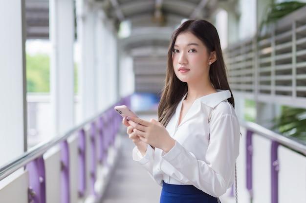 Asiatische schöne geschäftsfrau steht auf der überführung des skytrain in der stadt, während sie ihr smartphone benutzt