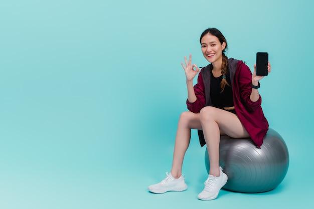 Asiatische schöne glückliche frau, die smartphone hält und auf sitzball nach der übung lokalisiert auf blau sitzt