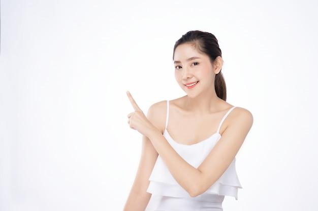Asiatische schöne junge frau, die eine hand mit dem finger auf oberseite mit lächelngesicht zeigt