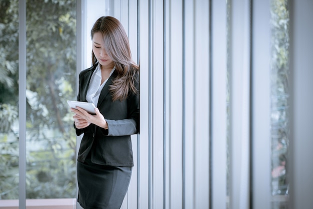 Asiatische schöne junge geschäftsfrau, die tablette verwendet, um im büro zu arbeiten