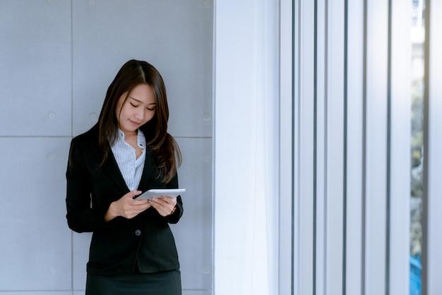 Asiatische schöne junge geschäftsfrau im anzugsrock unter verwendung der tablette, zum über verkaufs- und vermarktungsplan zu arbeiten