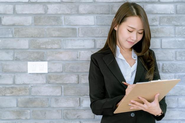 Asiatische schöne junge geschäftsfrau im anzugsrock unter verwendung des arbeitsdokuments über verkaufs- und marketingplan
