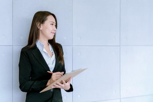 Asiatische schöne junge geschäftsfrau im anzugsrock unter verwendung des arbeitsdokuments über verkaufs- und vermarktungsplan
