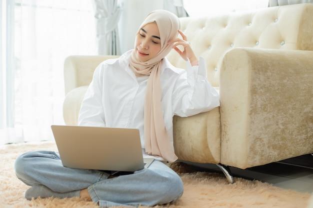 Asiatische schöne muslimische frauen arbeiten mit laptop, fernarbeit online und arbeiten von zu hause aus.