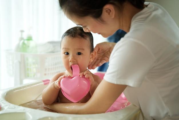 Asiatische schöne mutter, die kleines nettes baby hält und ein bad ihr kind sitzt in der badewanne im raum nimmt