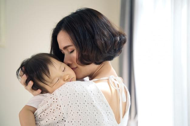 Asiatische schöne mutter, die schlafendes baby in ihren armen umarmt und leicht das kind küsst. die mutter schloss ihre augen, während sie ihren babykopf hielt, um sich auf der schulter auszuruhen. hauch von liebe und familiärer beziehung.