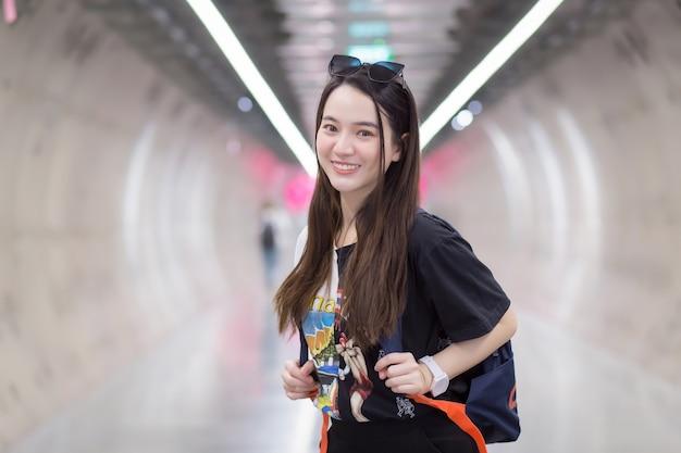 Asiatische schöne touristin, die ein schwarzes hemd trug, lächelte in einen u-bahn-tunnel und trug einen rucksack