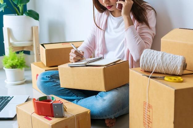 Asiatische schöne unternehmerin, die am telefon mit kunden spricht und die bestellung in notizbuch schreibt