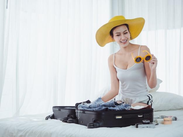 Asiatische schönheit bereiten taschen vor, um in den urlaub zu gehen