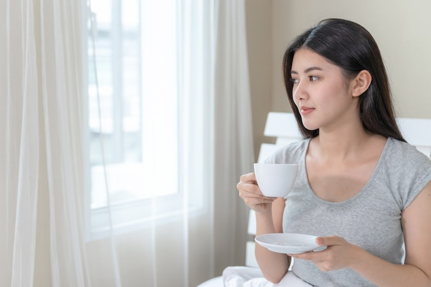 Asiatische schönheit, die auf bett im schlafzimmer sitzt und in der hand kaffeetasse hält