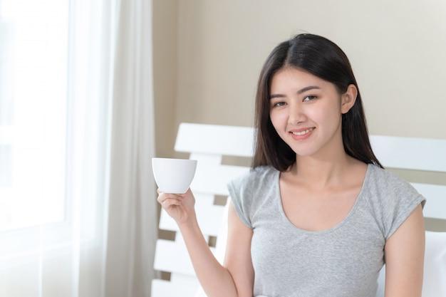 Asiatische schönheit, die auf bett im schlafzimmer sitzt und in der hand kaffeetasse mit glücklichem hält