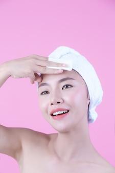 Asiatische schönheit, die das gesicht auf einem rosa hintergrund, einer kosmetologie und einem badekurort abwischt.