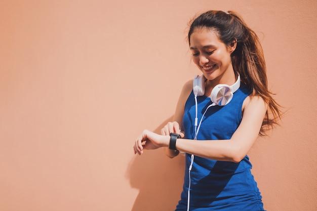 Asiatische schönheit, die intelligente uhr nach übung auf orange wand stillsteht und verwendet