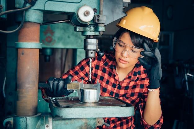 Asiatische schönheit, die mit maschine im fabrikingenieur- und arbeiterinkonzept oder im frauentag arbeitet
