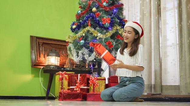 Asiatische schönheit freut sich über ein weihnachtsgeschenk zu hause