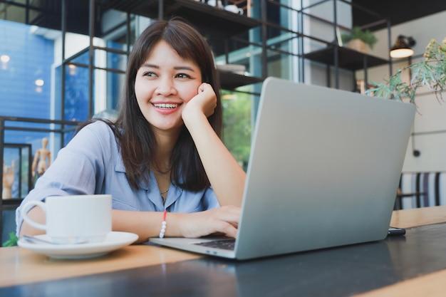 Asiatische schönheit im blauen hemd unter verwendung des laptops und des trinkenden kaffees