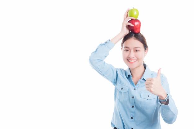 Asiatische schönheit setzte äpfel auf kopf und zeigt daumen oben über weißem hintergrund