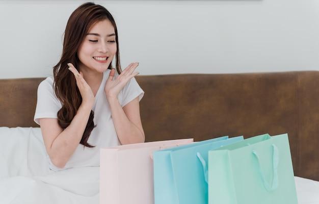 Asiatische schönheit überrascht von papiertüten mit waren