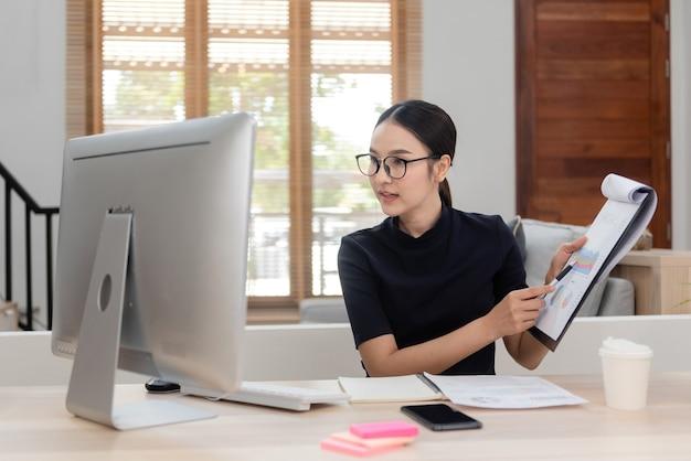 Asiatische schönheit von zu hause aus per computer arbeiten mit kollegen interagieren mit einem fröhlich lächelnden gesicht eine neue normale online-aktivität