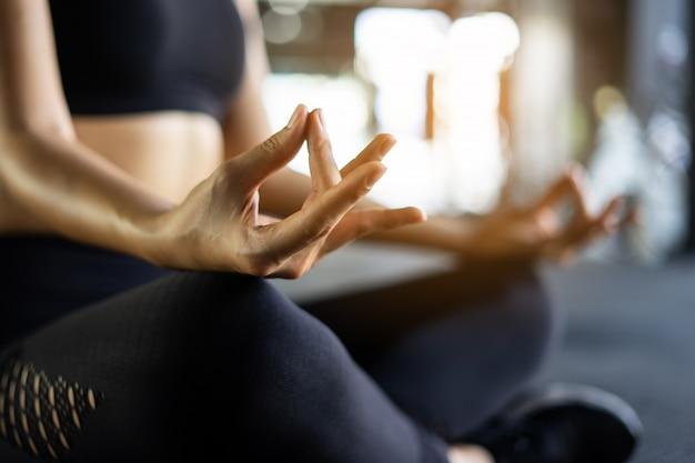 Asiatische schönheiten üben yoga mit meditation lotus in der eignungsturnhalle. übungskonzept und gesundheit für immer.