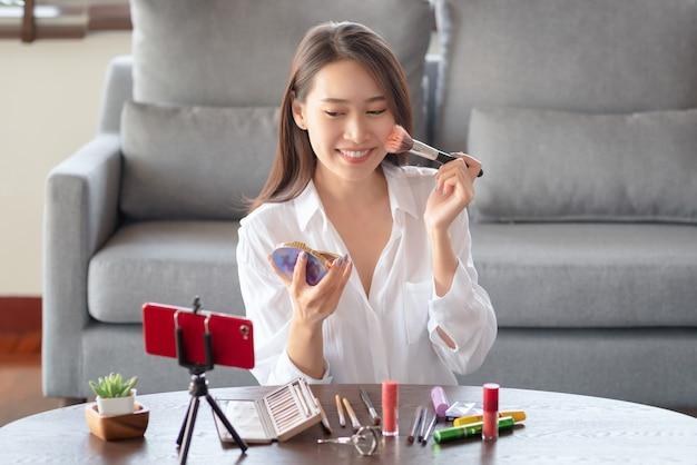 Asiatische schönheitsbeeinflusserin, die ein video-tutorial für ihren schönheitskanal über kosmetik erstellt, während sie zu hause sicher ist