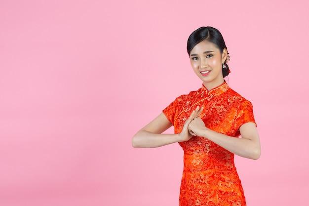 Asiatische schönheitsfrau mit glückwunschgeste im chinesischen neuen jahr new