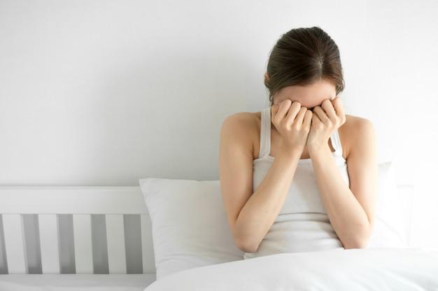 Asiatische schönheitsfrau schreit auf weißem schlafzimmer am morgen