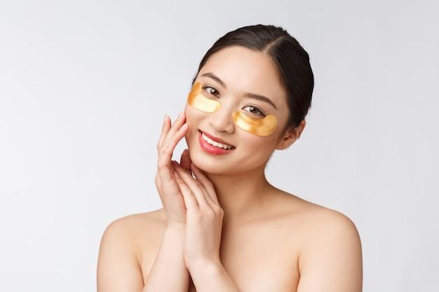 Asiatische schönheitsjugendfrau pflegt ihre haut mit goldaugenmaskenflecken unter den augen