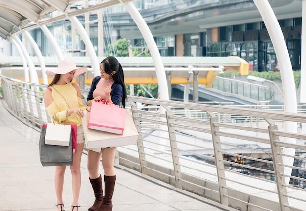 Asiatische schönheitsmädchen, die papiertüten mit glück und fröhlich nach dem einkaufen im kaufhaus halten