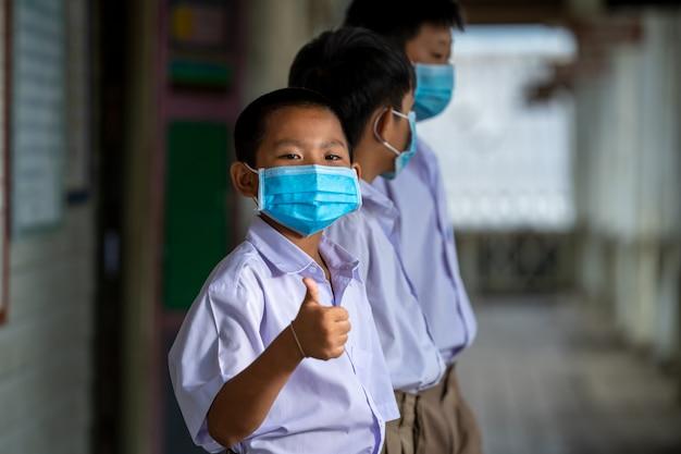 Asiatische schüler, die eine schutzmaske tragen, um sich gegen covid-19 zu schützen, öffnen ihre schule wieder, bildung, grundschule.