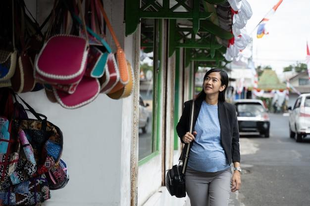 Asiatische schwangere frau, die taschen betrachtet