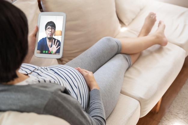 Asiatische schwangere frau, die videoanruf mit ihrem ehemann mit digitalem tablett macht
