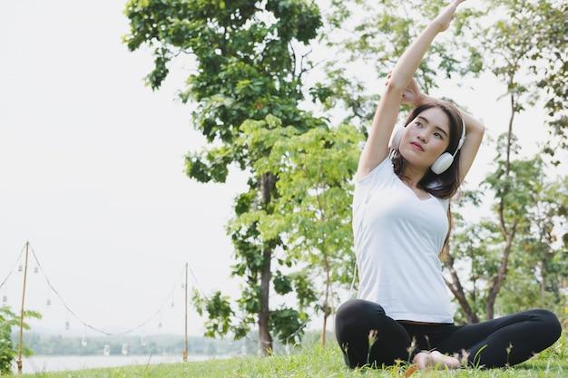Asiatische schwangere frau, die yoga praktiziert, während musik auf grünem gras im öffentlichen park hört.