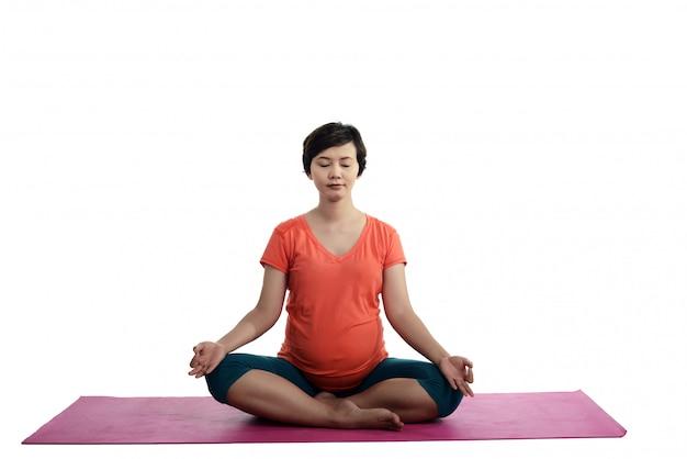 Asiatische schwangere frau, die yoga tut