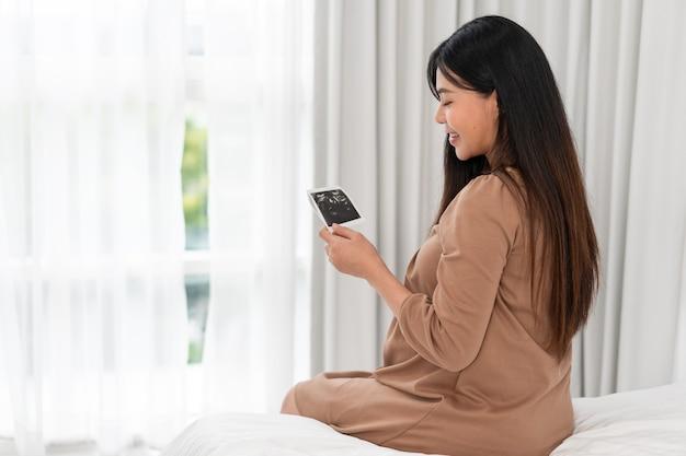 Asiatische schwangere frau im braunen kleid, die ultraschall auf ihrem bauch im bett im schlafzimmer hält. schwangerschaft, elternschaft, vorbereitungs- und erwartungskonzept