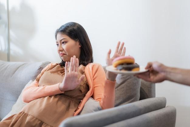 Asiatische schwangere frau lehnen junk food oder ungesunde lebensmittel wie donuts für ihre und babygesundheit ab. diät und gute gesundheit für mutterkonzept.